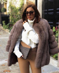 "A woman wearing a brown fox fur coat called ""Modena"" designed by MVFURS."