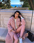 A woman wearing a pink genuine lambwool teddy coat designed by MVFURS.