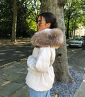 "A woman wearing a nude genuine parka called ""Elisa"" designed by MVFURS."