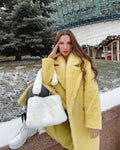 A woman wearing a yellow genuine lambwool teddy coat designed by MVFURS.