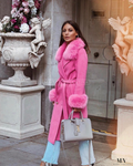 "A woman wearing a pink cashmere coat trimmed with fox fur collar and fur cuffs called ""London"" designed by MVFURS."