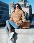 "A woman wearing a camel faux fur coat called ""Zoella"" designed by MVFURS"