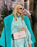 A woman wearing a turquoise genuine lambwool teddy coat designed by MVFURS.