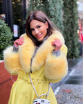 "A woman wearing a yellow leather coat with fox fur collar called ""Natelle"" designed by MVFURS."
