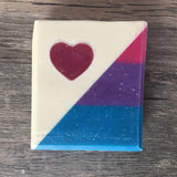 Handmade soap bar with a diagonal split, one half white with a pink heart, the other half bisexual pride flag stripes.