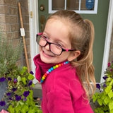 Munchables Rainbow Chew Necklace worn by young girl.