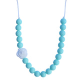 Munchables Chew Necklace with round light blue beads and a single white rose.