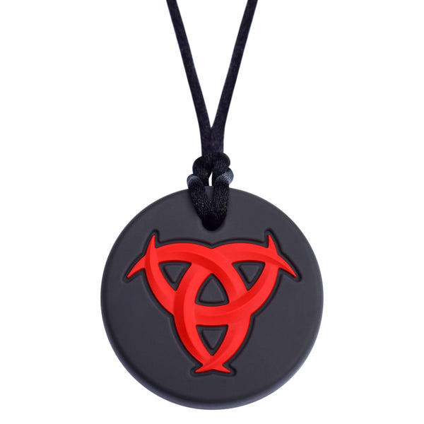 Munchables Celtic Chew Necklace with black background and red, raised design.