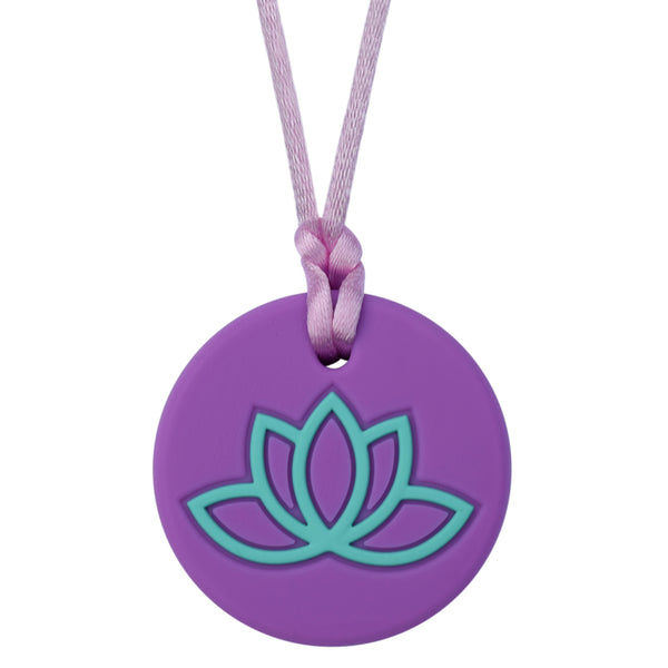 Munchables Lotus Chew Necklace with Purple Background and Aqua Design.