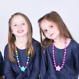 Two girls wearing Munchables Starlight Chew Necklaces.