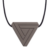An adult chew necklace in the shape of a triangle with smaller inset geometric triangles on the front-side. Shown in a warm gray colour on a black cord.