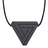 An adult chew necklace in the shape of a triangle with smaller inset geometric triangles on the front-side. Shown in a charcoal colour on a black cord.