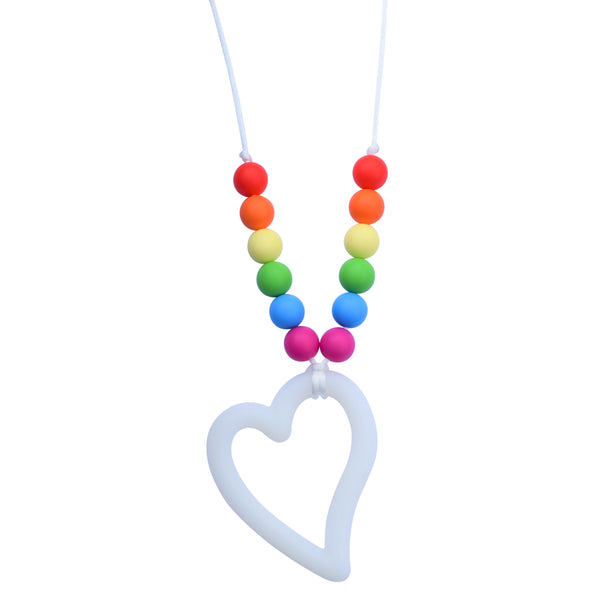 The Munchables Rainbow Heart Chew Necklace features a white heart pendant and 7 colourful round rainbow beads on each arm of the white cord.