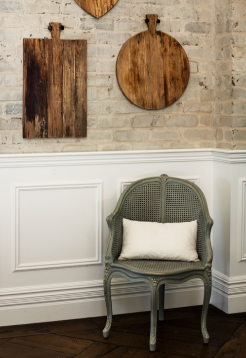 In the living room, a Dusty Luxe chair contrasts with the wainscoting and bagged brick walls.