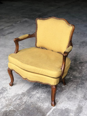 Pair of French Louis XV style yellow upholstered armchairs with low backs