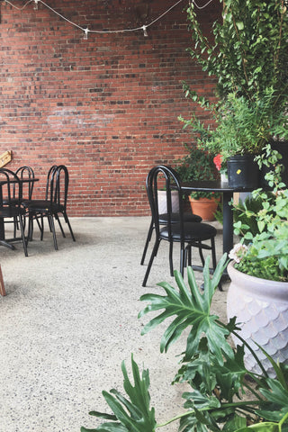 Factory Coffeehouse Covered Patio comes alive with plants during the warmer months.