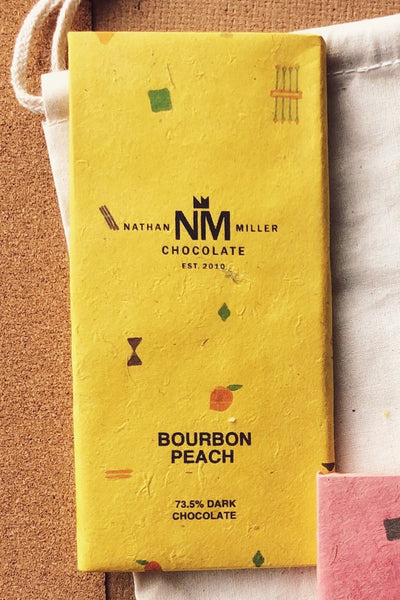 Bourbon Peach dark chocolate. Before the bar is made the cacao is aged in bourbon inside a barrel, the each notes will be more forward in flavor. Miller Chocolate bar. Label and photograph by Chelsea Russo.