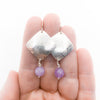 Sterling Goat Earrings with Cape Amethyst by Judie Raiford held in hand