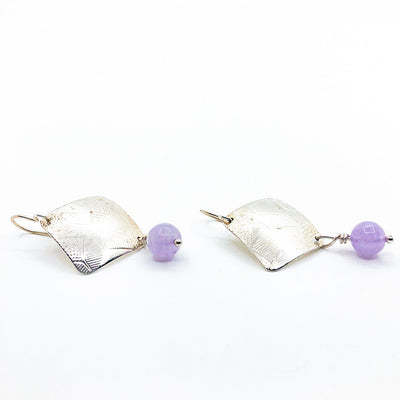 side angle view of Sterling Goat Earrings with Cape Amethyst by Judie Raiford