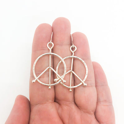sterling silver Small Hammered Peace Sign Earrings by Judie Raiford held in hand