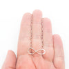 sterling silver Infinity Maggie Necklace by Judie Raiford held in hand