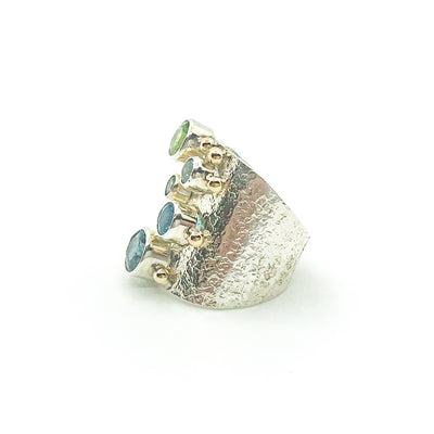 left side view of size 8.25 Brenda Big Girl Ring with sterling silver, 14k gold, 8mm London blue topaz, 7mm peridot, 6mm swiss blue topaz, 5.5 mm aquamarine, 4mm Montana sapphire by Judie Raiford