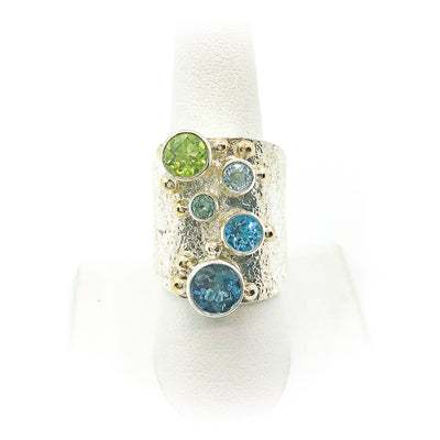 size 8.25 Brenda Big Girl Ring with sterling silver, 14k gold, 8mm London blue topaz, 7mm peridot, 6mm swiss blue topaz, 5.5 mm aquamarine, 4mm Montana sapphire by Judie Raiford on white ring display stand