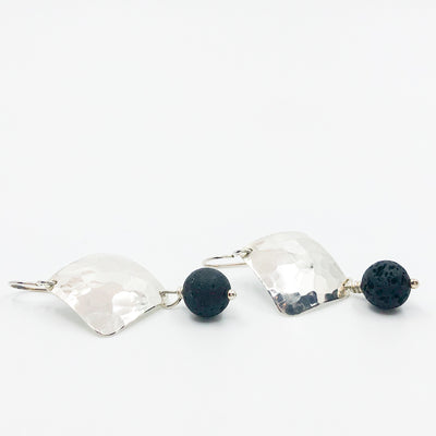 side angle flat lay of Sterling Ball Pein Hammered Goat Earrings with black lava by Judie Raiford