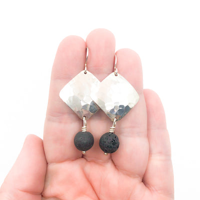 Sterling Ball Pein Hammered Goat Earrings with black lava by Judie Raiford held in hand