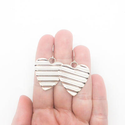 Large Sterling Silver Corrugated Heart Earrings by Judie Raiford held in hand