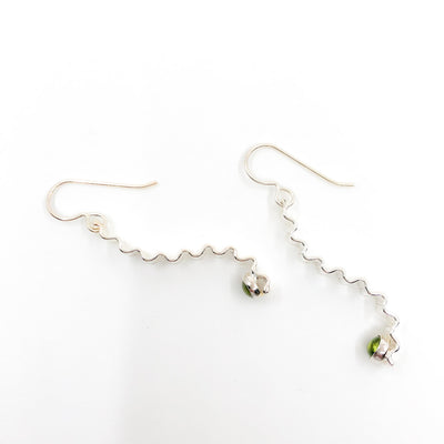 side angle view of Short Sterling Corrugated Wave Stick Ears with Peridot and french hook by Judie Raiford