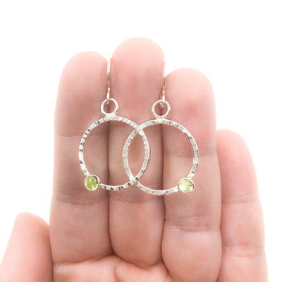 Sterling Pluto Earrings with Peridot by Judie Raiford held in hand