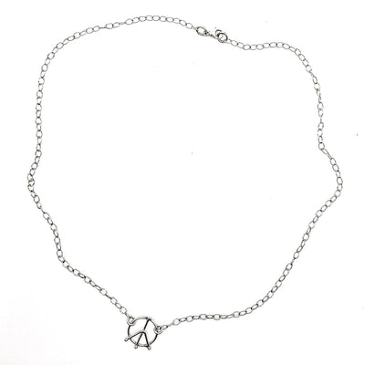 flat lay of sterling silver Tiny Peace Sign Necklace by Judie Raiford