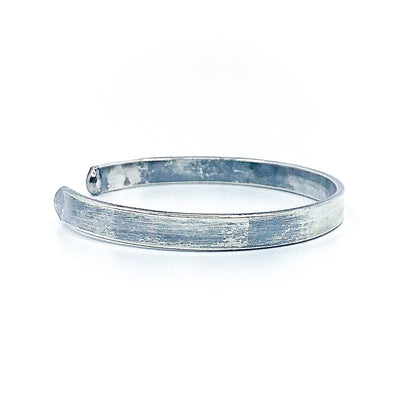right side view of Oxidized Sterling Flat Band Cuff with Paw Print by Judie Raiford