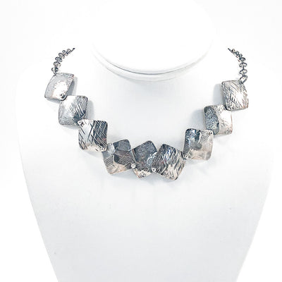 Oxidized Sterling Traveling Squares Necklace by Judie Raiford on white display mannequin