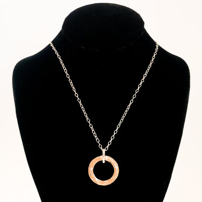 Sterling and 14k Gold Filled Ball Pein Hammered Circle Pendant Necklace by Judie Raiford displayed on black mannequin bust
