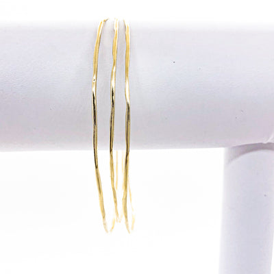 14k Gold Filled Skinny 3-Piece Bangle Set by Judie Raiford hanging on white bracelet display stand