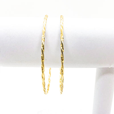 pair of 14k Gold Filled Single Twist Bangle by Judie Raiford handing on white bracelet display stand