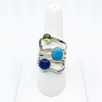 size 11 Sterling Wrap Ring with Peridot, Lapis, and Turquoise by Judie Raiford on white ring display stand