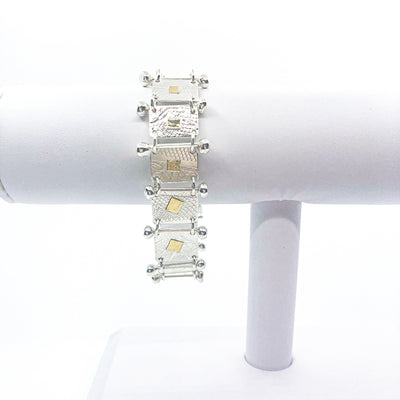 Sterling and 22k Singer Bracelet by Judie Raiford hanging on white bracelet display stand