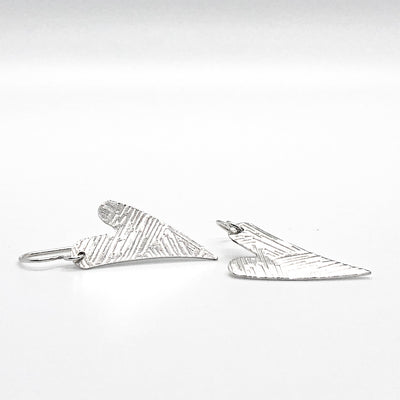 side angle view of Sterling Silver Textured Heart Earrings by Judie Raiford