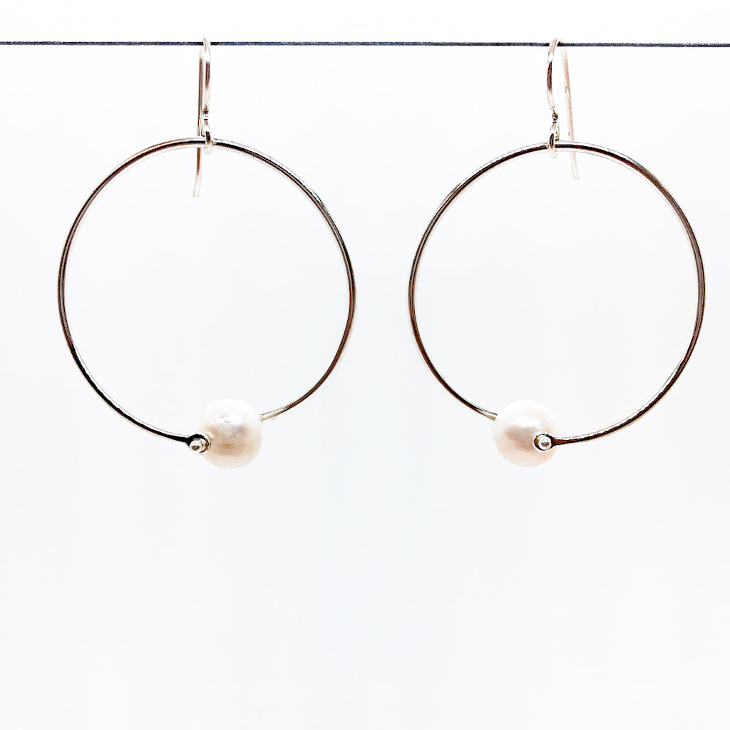 Sterling Twisted Hoop Pearl Earrings by Judie Raiford hanging on a wire