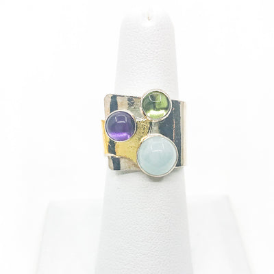 size 8 Sterling and 24k Gold Crotch Hugger Ring with Aquamarine, Peridot, and Amethyst by Judie Raiford on white ring display stand