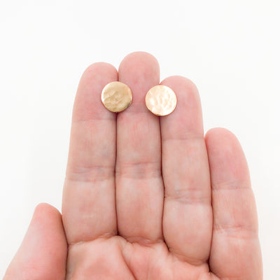 14k Gold Filled Textured Circle Stud Earrings by Judie Raiford held in hand
