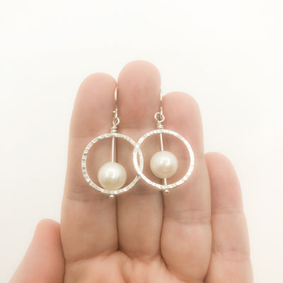 Sterling Not Naught Round Pearl Earrings with White Pearls by Judie Raiford held in hand