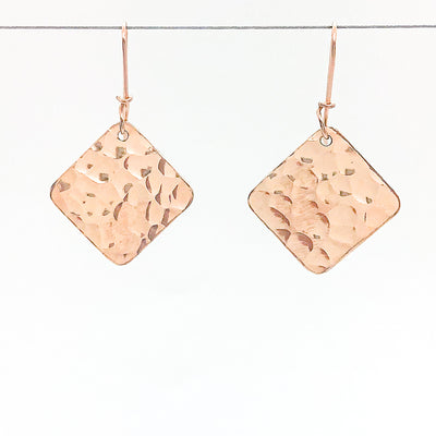 14k Rose Gold Ball Pein Square Earrings by Judie Raiford hanging on a wire