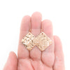14k Rose Gold Ball Pein Square Earrings by Judie Raiford held in hand