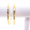 pair of 14k Gold Filled Ball Pein Hammered Bangles by Judie Raiford hanging on white bracelet display stand
