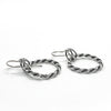 side angle view of polished and oxidized sterling silver Double Twist Hoop Earrings by Judie Raiford