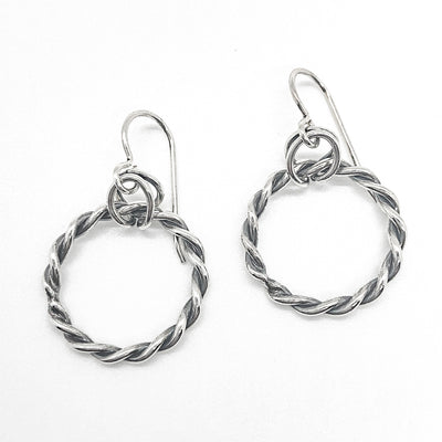 flat lay view of polished and oxidized sterling silver Double Twist Hoop Earrings by Judie Raiford